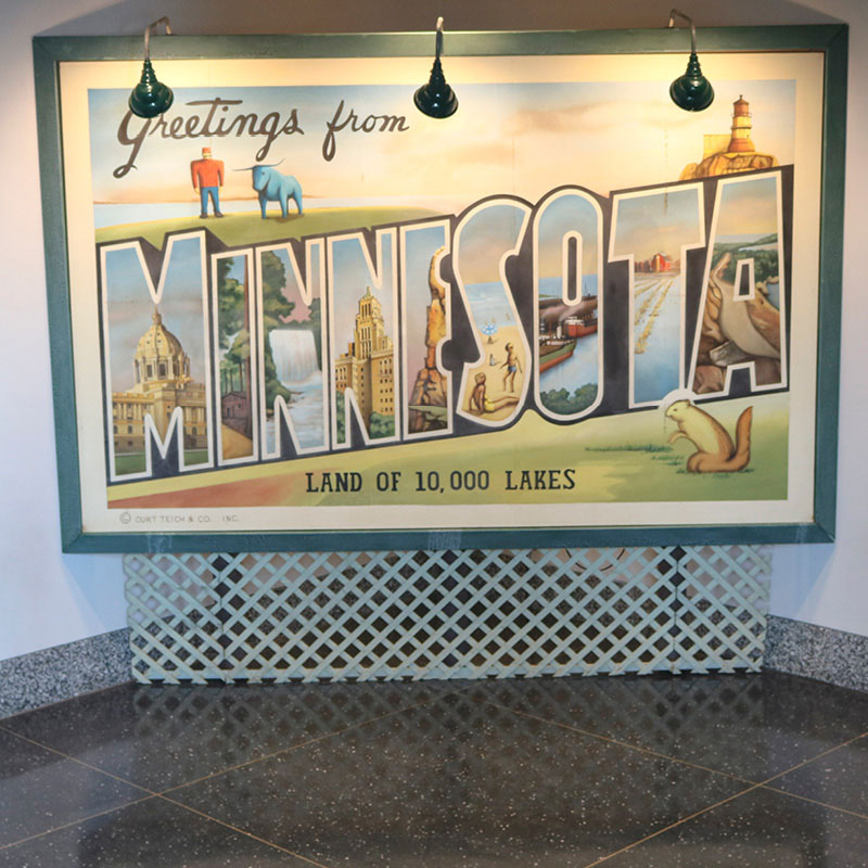 A large display in the style of a postcard, with the words: Greetings from Minnesota. Land of 10,000 lakes.