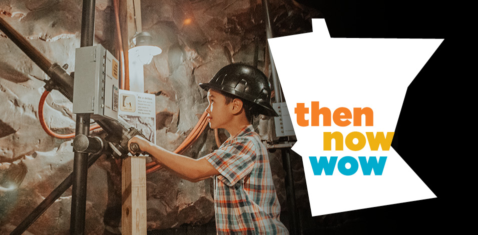 A boy in a hard hat pretends to drill in the mining area of the Then Now Wow exhibit.